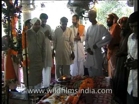 Devotees offer money and clothes at mausoleum of Hindu Saint