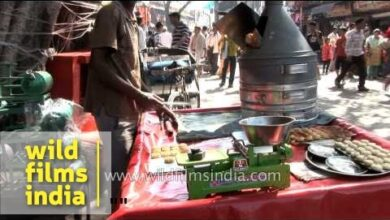 Man baking cookies in typical coal fired oven in Haridwar market